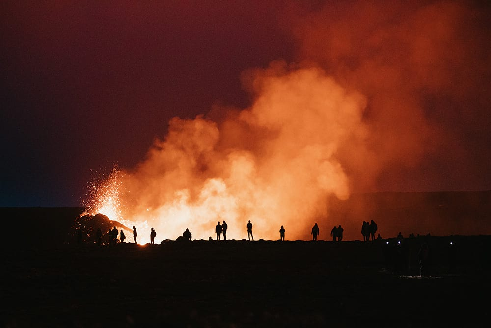 Fagradalsfjall volcano eruption with visitors in telescope lens