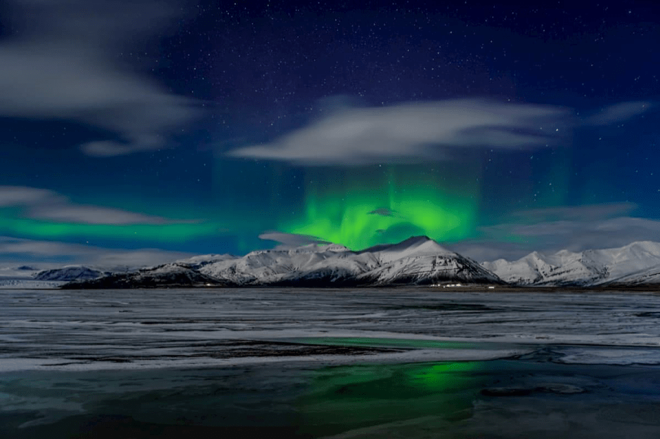 Beautiful northern lights shining over snowy mountains in Iceland