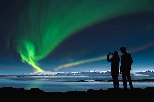two people photographing northern lights