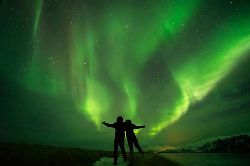 two people silhouetted against a sky with green northern lights
