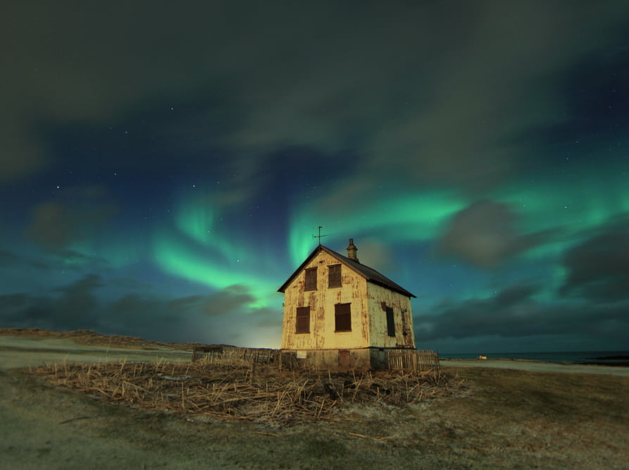 adandoned white house under blue northern lights