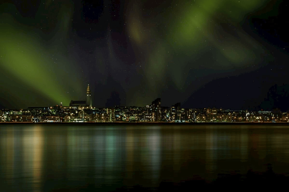 Northern Lights shining over downtown Reykjavik, Iceland. See them on a northern lights tour with Gray Line Iceland