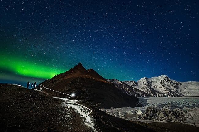 People-taking-pictures-of-northern-lights-at-glacier